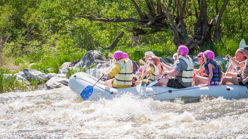 trasportare Società allegra della gente delle età differenti che navigano su una barca gonfiabile di gomma teamwork Emozioni posi immagini stock libere da diritti