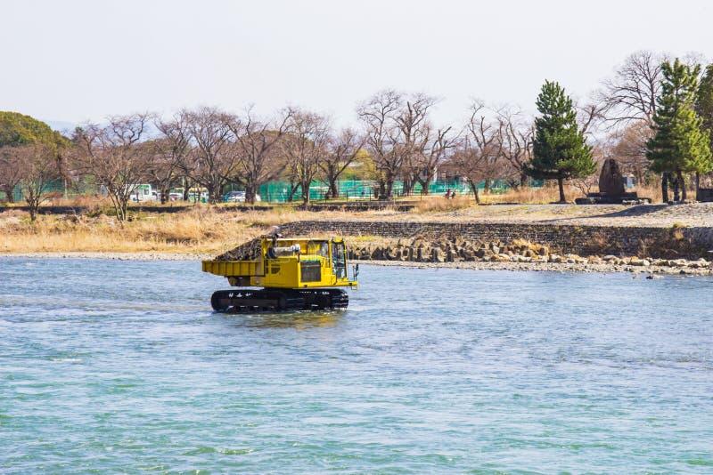 Trasporti e pietra di dragaggio in fiume Katsura per fare lo scorrimento dell'acqua fotografia stock