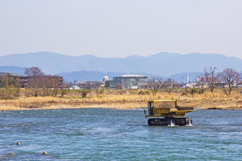 Trasporti e pietra di dragaggio in fiume Katsura per renderlo allo scorrimento dell'acqua ` s facile a Kyoto immagine stock
