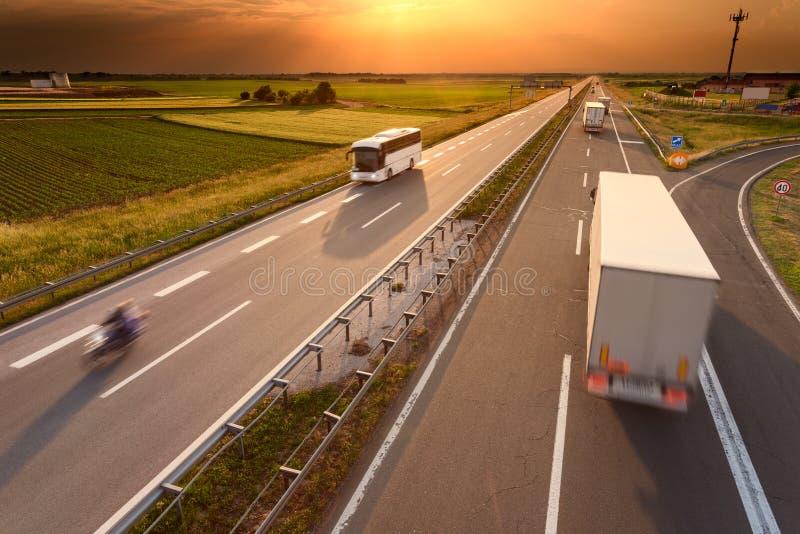 Trasporti il bus ed il motociclo su autocarro sull'autostrada al tramonto fotografia stock libera da diritti