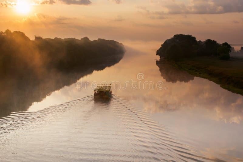 Trasporti il galleggiamento con una zattera sul fiume all'alba su una mattina nebbiosa fotografia stock libera da diritti