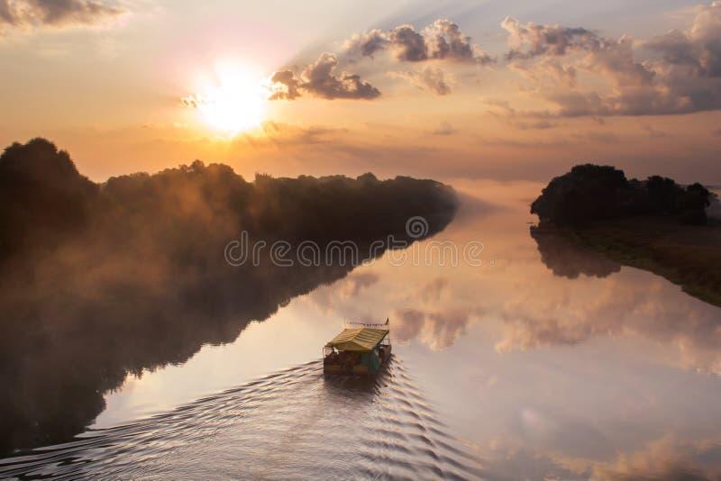 Trasporti il galleggiamento con una zattera sul fiume all'alba su una mattina nebbiosa fotografia stock