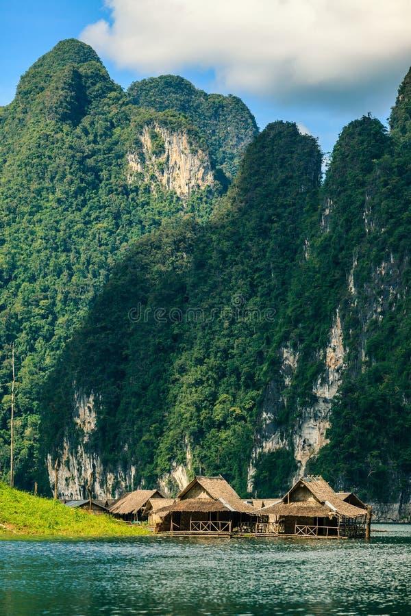 Trasporti la casa con una zattera sul fiume con la montagna su fondo immagine stock