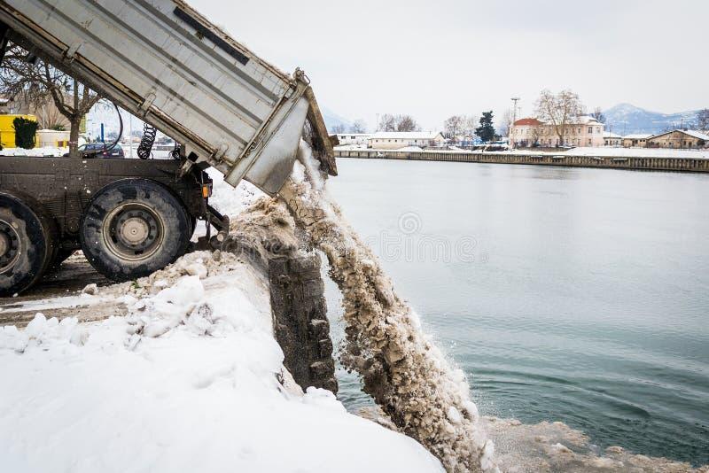 Trasporti lo scarico su autocarro della neve nel fiume immagini stock