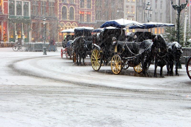 Trasporto dei cavalli con la vettura antiquata nell'ambito delle precipitazioni nevose sul quadrato vuoto in Europa Fondo di viag fotografie stock libere da diritti