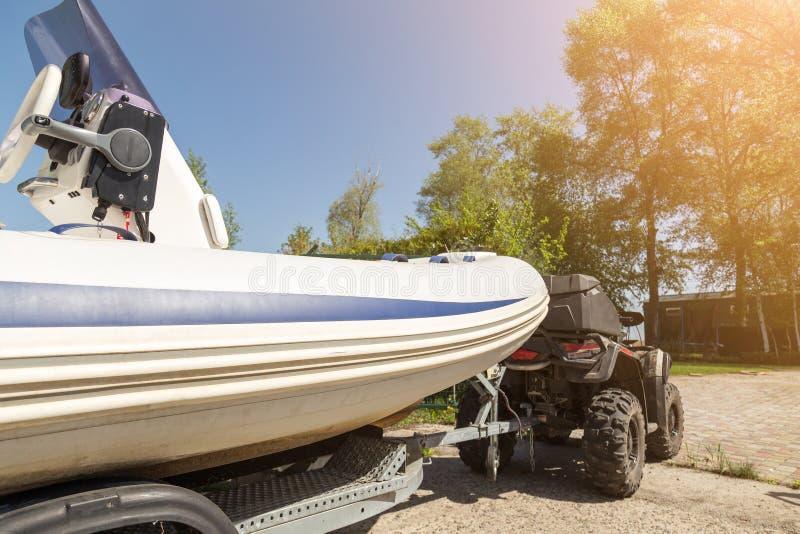 Trasporto della barca gonfiabile sul rimorchio I movimenti del quadbike di ATV spediscono alla riva del fiume o del lago per lanc immagini stock libere da diritti