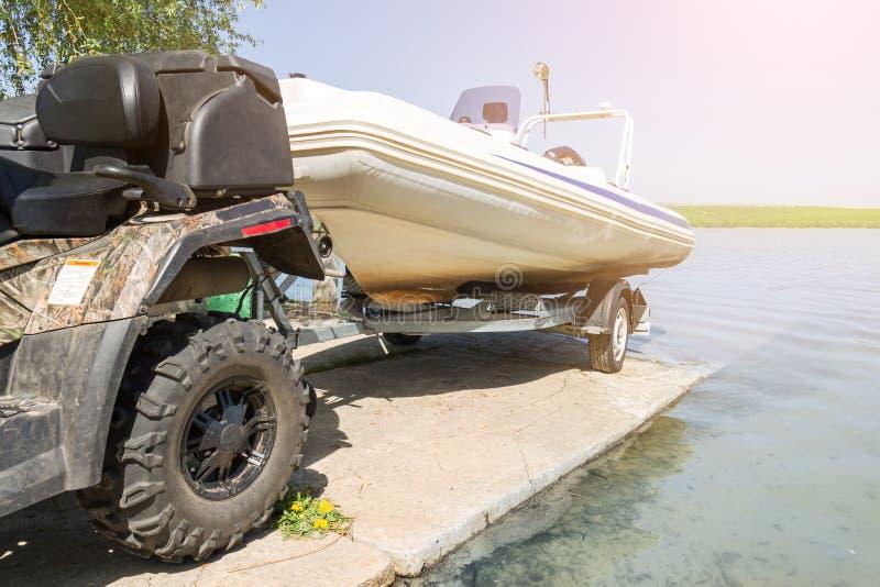 Trasporto della barca gonfiabile sul rimorchio I movimenti del quadbike di ATV spediscono alla riva del fiume o del lago per lanc fotografie stock
