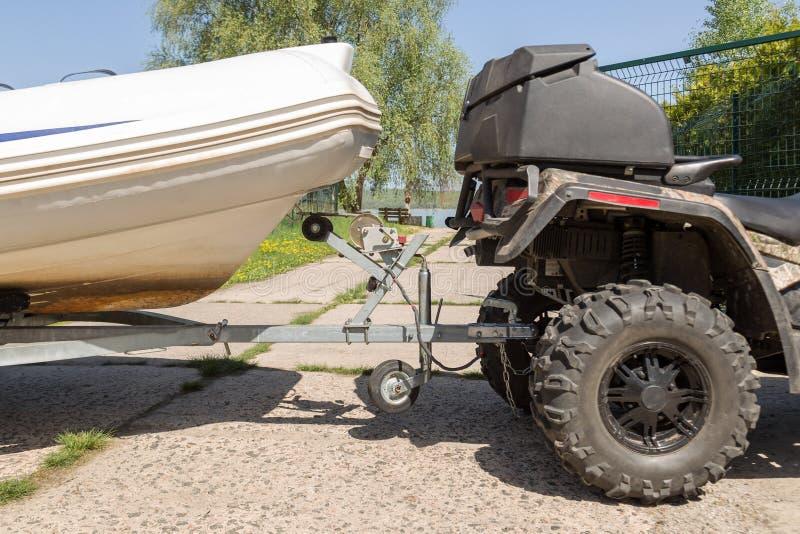 Trasporto della barca gonfiabile sul rimorchio I movimenti del quadbike di ATV spediscono alla riva del fiume o del lago per lanc immagini stock