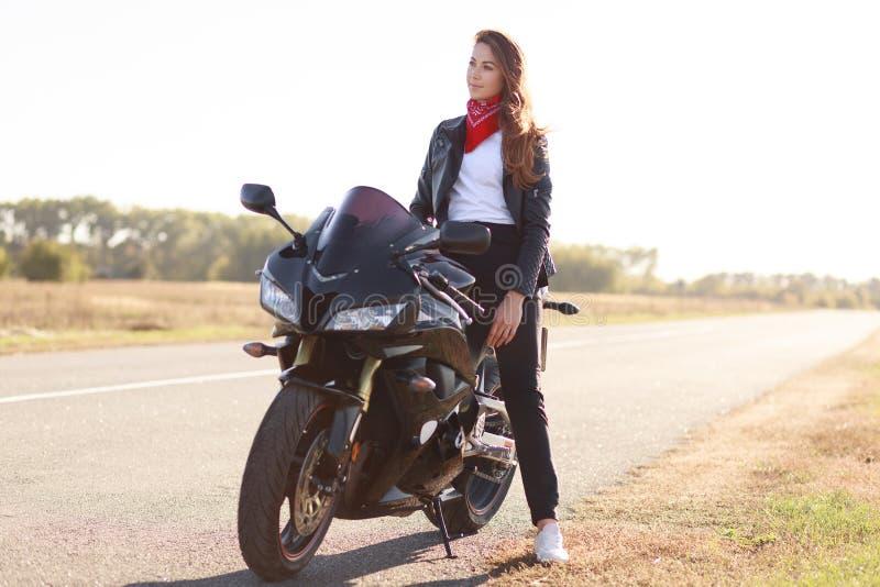 Trasporto e concetto estremo Il motociclista femminile alla moda premuroso gode dell'alta velocità, posa sulla bici veloce, respi fotografie stock
