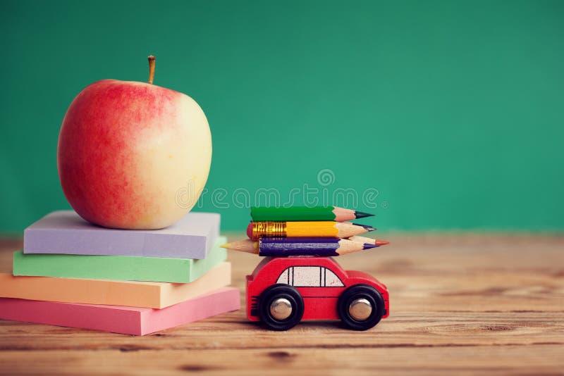 Trasporto rosso miniatura dell'automobile matite variopinte e carte rosse della pila e della mela sulla tavola di legno Di nuovo  fotografie stock