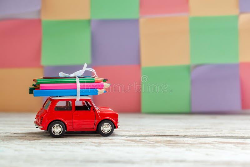 Trasporto rosso miniatura dell'automobile matite variopinte sulla tavola di legno Di nuovo al concetto del banco immagini stock libere da diritti