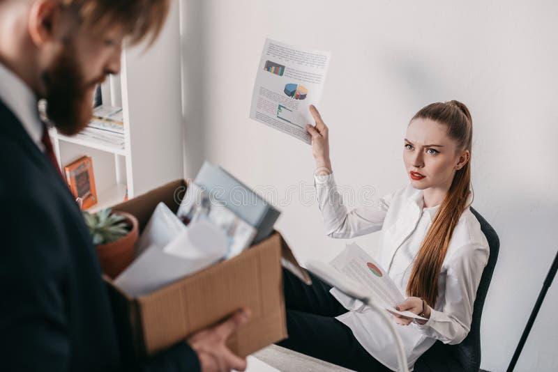 Trastorne al hombre de negocios encendido con la caja de cartón y la empresaria enojada en oficina imagen de archivo libre de regalías