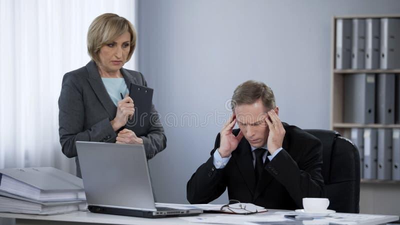 Trastorne al hombre de negocios subrayado que sufre del dolor de cabeza, encontrando con a la secretaria imagenes de archivo