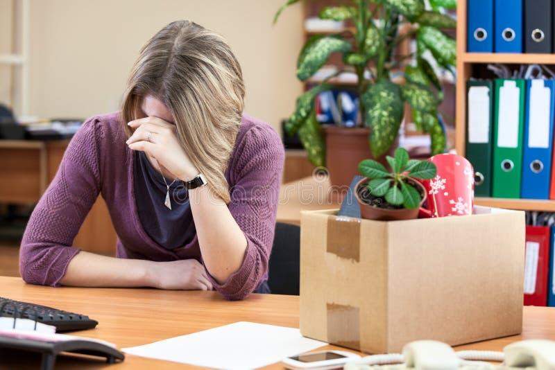 Trastorno con la mujer del despido que llora en el lugar de trabajo foto de archivo