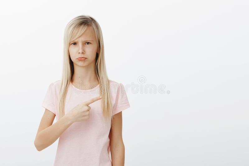 Trastorno de la muchacha y celoso, queriendo el nuevo juguete Retrato del niño melancólico descontentado triste con el pelo rubio fotografía de archivo