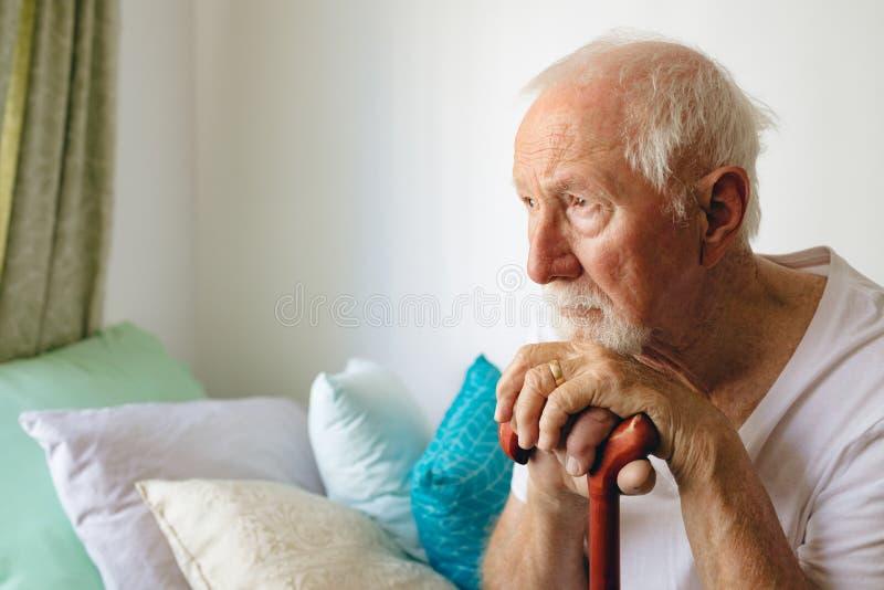 Trastorno que se sienta del paciente masculino mayor en cama con el palillo en la casa de retiro fotos de archivo libres de regalías