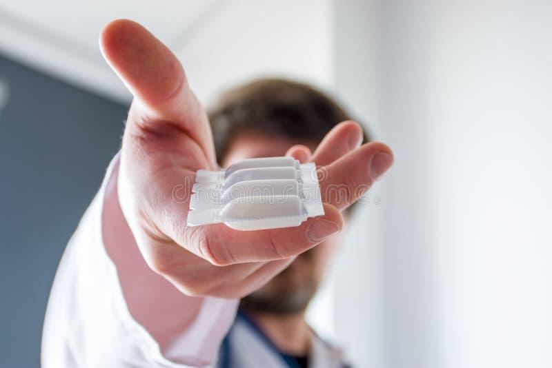 Tratamento com medicação sob a forma de supositórios fotografia de conceito Médico segurando em sua mão estendida embalagens de s fotos de stock