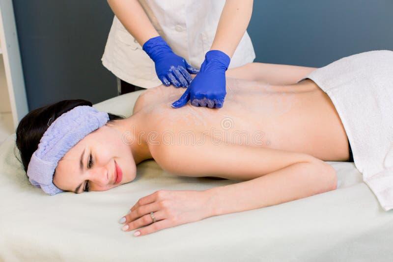Tratamento da beleza Morena nova que obt?m a massagem traseira no sal?o de beleza dos termas imagens de stock
