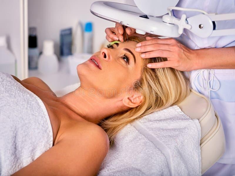 Tratamento da sobrancelha da mulher de meia idade no salão de beleza dos termas imagem de stock royalty free