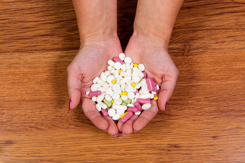 Tratamento das doenças com métodos modernos Homeopaticamente e produtos químicos Vários tipos das drogas nas mãos fêmeas fotografia de stock royalty free