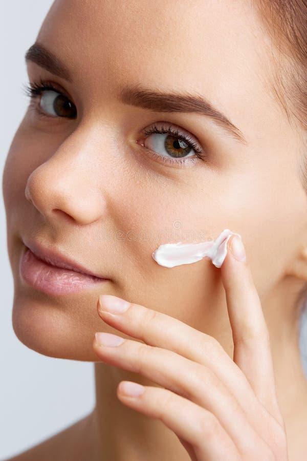 Tratamento de creme cosmético de aplicação modelo bonito em sua cara A cara bonita nova do close-up da aplicação da menina hidrat imagens de stock royalty free