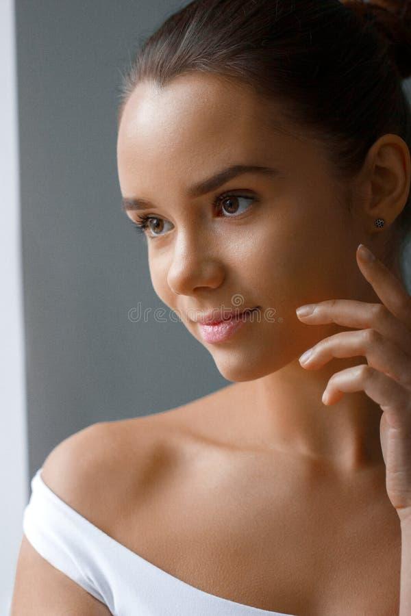 Tratamento de creme cosmético de aplicação modelo bonito em sua cara no fundo branco Cuidado de pele Mulher que usa a almofada de fotos de stock