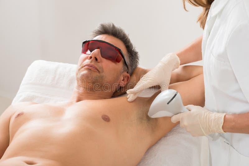 Tratamento de Giving Hair Removal do esteticista ao homem foto de stock royalty free