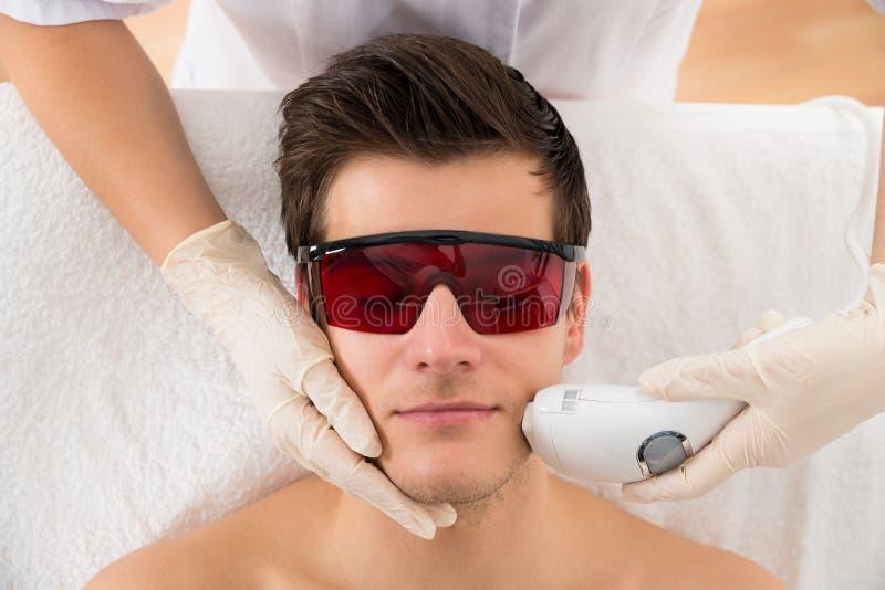 Tratamento de Giving Laser Epilation do esteticista para equipar a cara imagem de stock