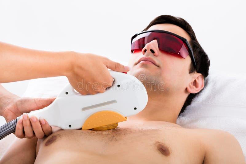 Tratamento de Giving Laser Epilation do terapeuta ao homem imagem de stock