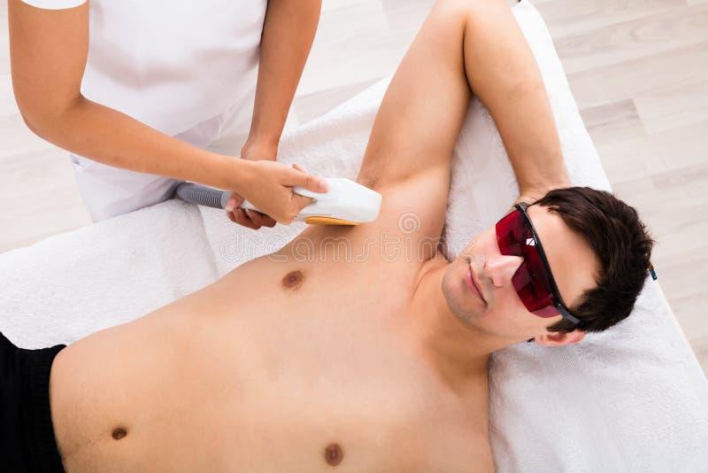 Tratamento de Giving Laser Epilation do terapeuta na axila do ` s do homem imagens de stock