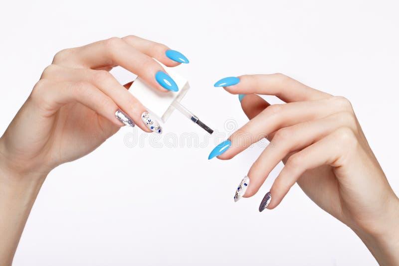 Tratamento de mãos azul do verão bonito na mão fêmea com óleo para cutículas Close-up fotografia de stock