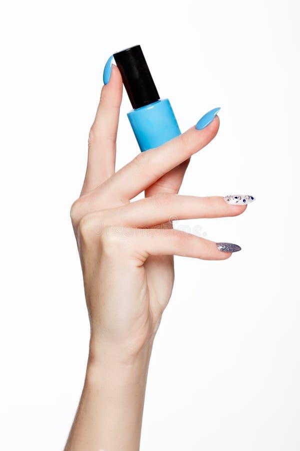 Tratamento de mãos azul do verão bonito na mão fêmea com verniz para as unhas Close-up foto de stock