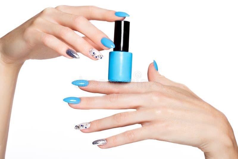 Tratamento de mãos azul do verão bonito na mão fêmea com verniz para as unhas Close-up imagens de stock royalty free
