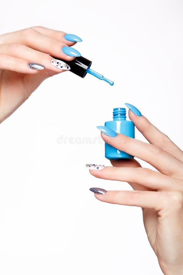 Tratamento de mãos azul do verão bonito na mão fêmea com verniz para as unhas Close-up imagens de stock