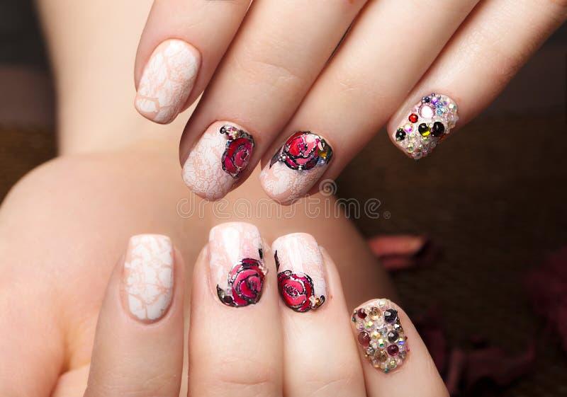 Tratamento de mãos bonito com as flores nos dedos fêmeas Projeto dos pregos Close-up imagens de stock