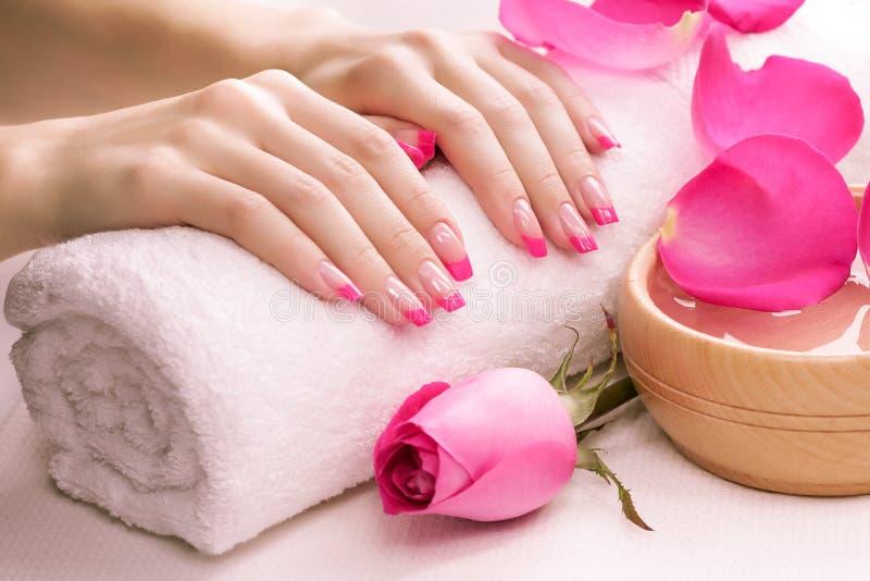Tratamento de mãos cor-de-rosa com toalha. Termas imagem de stock