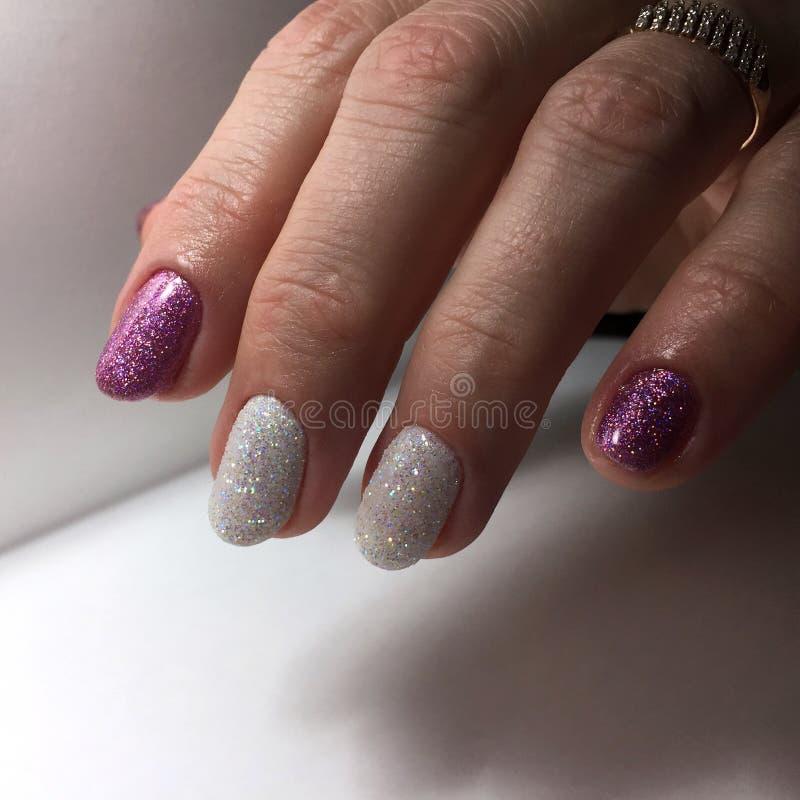 Tratamento de mãos de cores diferentes em pregos Tratamento de mãos fêmea na mão fotografia de stock royalty free