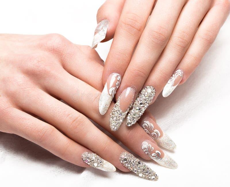Tratamento de mãos do casamento de Beautifil para a noiva em tons delicados com cristal de rocha Projeto do prego Close-up imagens de stock royalty free