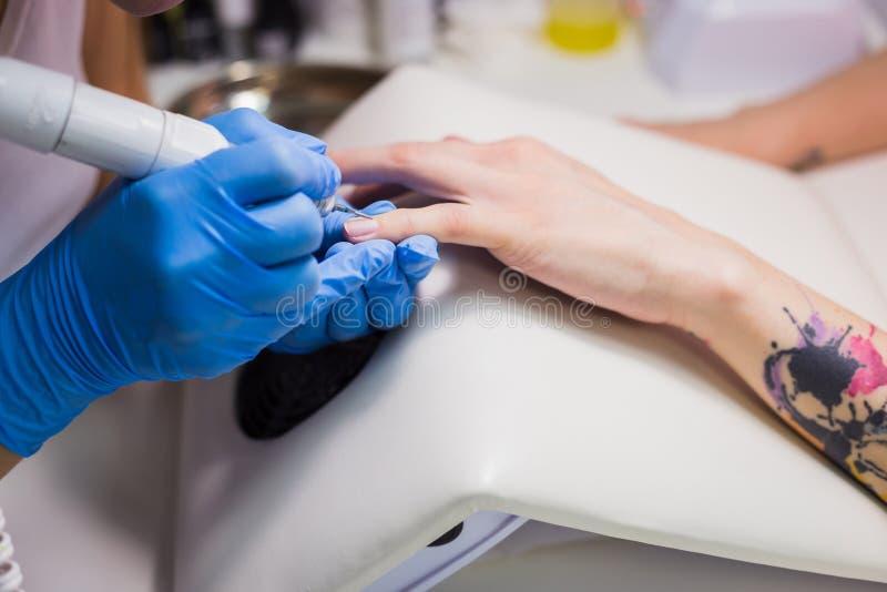 Tratamento de mãos do hardware em um salão de beleza O manicuro está aplicando a broca elétrica do arquivo de prego imagem de stock royalty free