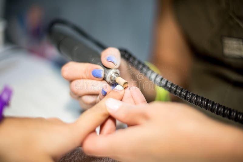 Tratamento de mãos do hardware Remoção do verniz velho do gel no salão de beleza O procedimento fazendo mestre da beleza do trata fotografia de stock