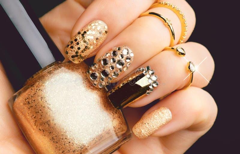Tratamento de mãos dourado da arte do prego com gemas e sparkles foto de stock