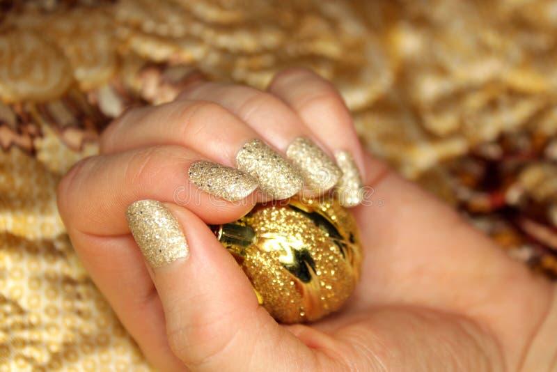 Tratamento de mãos dourado do prego de ano novo foto de stock