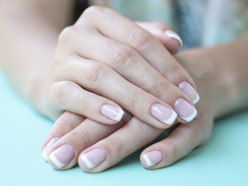 Tratamento de mãos francês fêmea do close up em um salão de beleza Pregos da mulher da beleza em um fundo da hortelã foto de stock royalty free