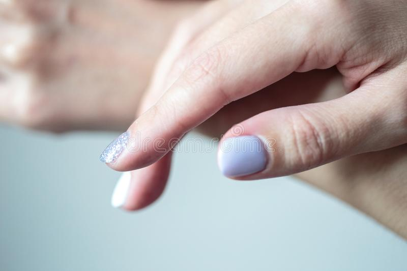 Tratamento de mãos lindo, verniz para as unhas macio pastel da cor, foto do close up fotografia de stock
