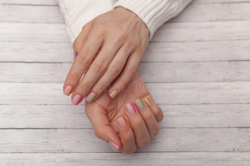 Tratamento de mãos moderno colorido, projeto do prego Modo do ver?o close-up no fundo de madeira imagem de stock