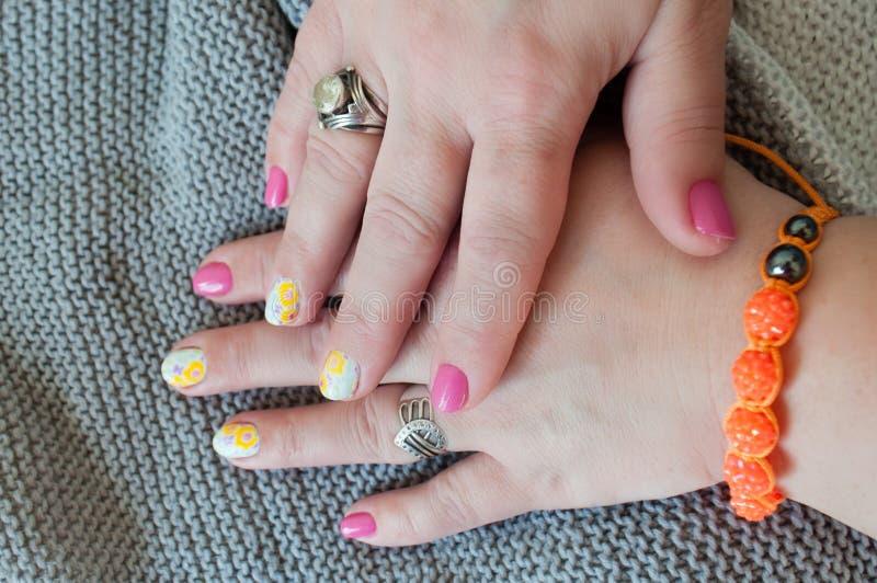 Tratamento de mãos na moda elegante à moda para mulheres As mãos bonitas fecham-se acima no fundo feito malha cinzento fotos de stock royalty free