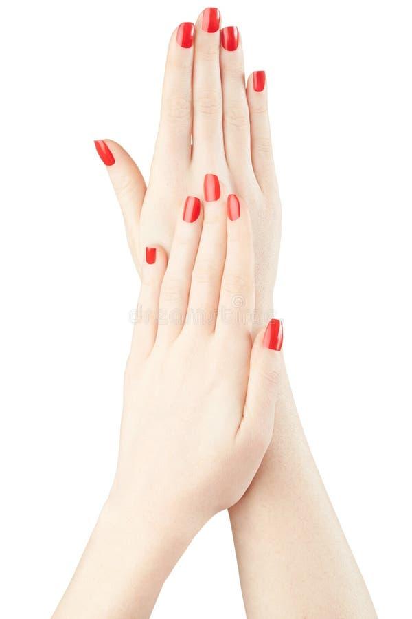 Tratamento de mãos nas mãos da mulher com verniz para as unhas vermelho imagem de stock