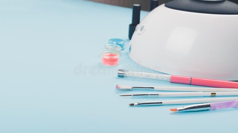 Tratamento de mãos, projeto da arte do prego ajustado no fundo azul Candeeiro de mesa profissional do diodo emissor de luz para o imagens de stock royalty free