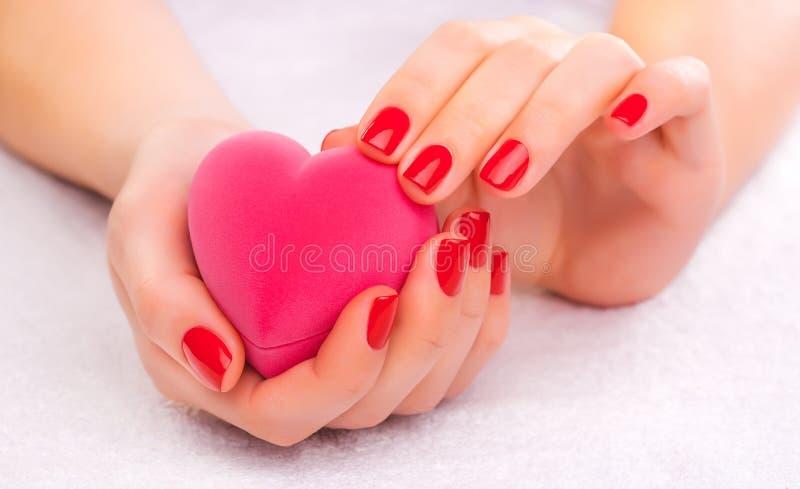 Tratamento de mãos vermelho com a caixa de presente na toalha branca fotos de stock royalty free