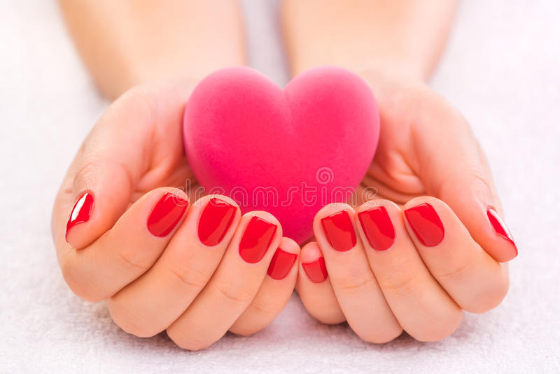 Tratamento de mãos vermelho com a caixa de presente na toalha branca imagens de stock